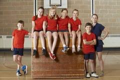 Ritratto della palestra Team Sitting On Vaulting Horse della scuola immagine stock libera da diritti