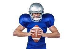 Ritratto della palla aggressiva della tenuta del giocatore di football americano immagine stock