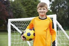 Ritratto della palla della tenuta del custode di scopo sul passo di calcio della scuola Fotografia Stock Libera da Diritti