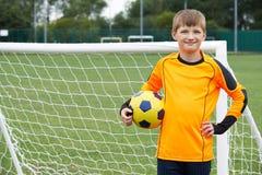 Ritratto della palla della tenuta del custode di scopo sul passo di calcio della scuola Fotografie Stock Libere da Diritti