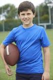 Ritratto della palla della tenuta del ragazzo sul campo da calcio della scuola immagini stock
