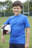 Ritratto della palla della tenuta del ragazzo sul passo di rugby della scuola Fotografie Stock