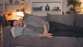 Ritratto della persona che fa un sonnellino sul sofà a casa alla notte con telecomando a disposizione archivi video