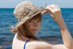 Ritratto della persona femminile attraente in cappello del vasto-bordo contro la s immagine stock
