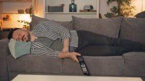 Ritratto della persona stanca che dorme sullo strato da solo che tiene il telecomando della TV archivi video