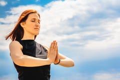 Ritratto della posizione di rilassamento di yoga della donna attraente di forma fisica contro il fondo del cielo fotografia stock libera da diritti
