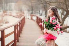 Ritratto della primavera della ragazza del bambino con il mazzo dei tulipani sulla passeggiata Fotografia Stock