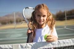Ritratto della racchetta e della palla di tennis della tenuta della ragazza Fotografia Stock Libera da Diritti