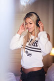Ritratto della ragazza abbastanza felice con le cuffie che ascolta la musica pop Fotografie Stock