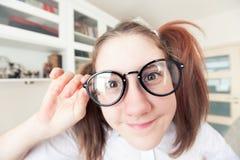 Ritratto della ragazza abbastanza nerd divertente con le code di cavallo in vetri Fotografia Stock
