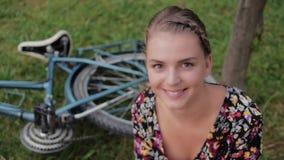 Ritratto della ragazza abbastanza sveglia che sorride accanto alla sua bici nel parco con le palme un giorno soleggiato archivi video