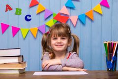 Ritratto della ragazza adorabile in aula Piccola scolara che si siede ad uno scrittorio e ad uno studio Fotografia Stock Libera da Diritti