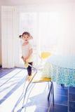 Ritratto della ragazza adorabile del bambino in vestito bianco con le trecce dei capelli ricci che stanno sulla sedia in cucina c Fotografie Stock