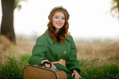 Ritratto della ragazza adulta in cappotto verde con la valigia immagini stock libere da diritti