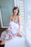 Ritratto della ragazza affascinante che si siede sul davanzale Immagini Stock