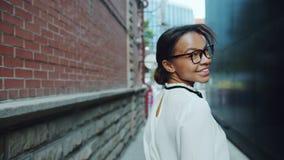 Ritratto della ragazza afroamericana graziosa che cammina all'aperto poi esaminando macchina fotografica archivi video