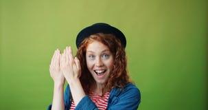 Ritratto della ragazza allegra che gioca nascondino che sorride sul fondo verde archivi video