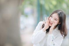 Ritratto della ragazza asiatica con il sorriso bianco della camicia e di gridare nello stile d'annata del film della natura all'a fotografia stock