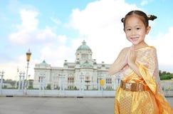Ritratto della ragazza asiatica del bambino in vestito tailandese tradizionale che prega contro il palazzo reale tailandese di Du immagine stock libera da diritti