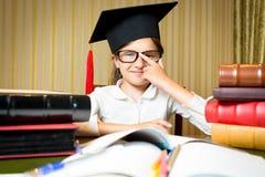 Ritratto della ragazza astuta in occhiali della tenuta del cappuccio di graduazione Fotografie Stock