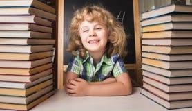 Ritratto della ragazza astuta sveglia che sorride mentre sedendosi Fotografia Stock