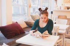 Ritratto della ragazza attraente che gode di buon caffè della tazza e del libro che si siede nell'interno comodo Immagini Stock