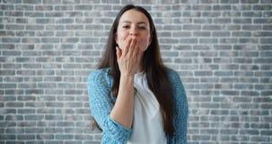 Ritratto della ragazza attraente che invia bacio dell'aria che sbatte le palpebre sorridere sul fondo del mattone video d archivio