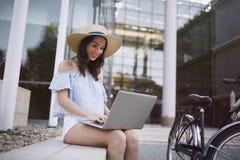 Ritratto della ragazza attraente che per mezzo del computer portatile Fotografia Stock