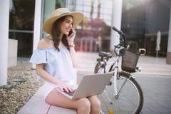 Ritratto della ragazza attraente che per mezzo del computer portatile Immagini Stock Libere da Diritti