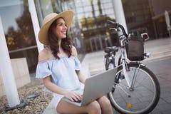 Ritratto della ragazza attraente che per mezzo del computer portatile Immagini Stock