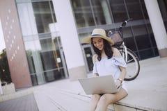 Ritratto della ragazza attraente che per mezzo del computer portatile Fotografie Stock