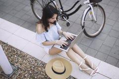 Ritratto della ragazza attraente che per mezzo del computer portatile Immagine Stock Libera da Diritti
