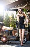 Ritratto della ragazza attraente di modo con il foulard e degli occhiali da sole oltre ad un vecchio motorino Immagini Stock