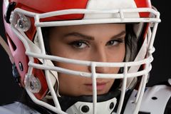 Ritratto della ragazza attraente sexy con un trucco luminoso in un'attrezzatura di sport per rugby con il casco sulla testa che g fotografia stock