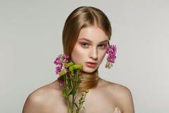 Ritratto della ragazza bionda fresca e bella con i fiori rosa fotografia stock libera da diritti