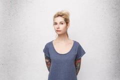 Ritratto della ragazza bionda seria che guarda direttamente in camera incrocio le sue mani indietro Maglietta blu casuale d'uso Fotografia Stock