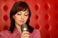 Ritratto della ragazza in camicia rossa con il microfono Fotografie Stock Libere da Diritti