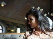 Ritratto della ragazza castana attraente con un bello sorriso all'interno fotografia stock