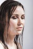 Ritratto della ragazza castana caucasica con gli occhi chiusi che mostrano pelle bagnata e brillante e capelli bagnati Immagini Stock