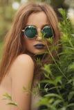 Ritratto della ragazza castana con le labbra blu in occhiali da sole rotondi Fotografie Stock Libere da Diritti