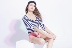 Ritratto della ragazza castana esile caucasica sensuale che posa in abbigliamento della via contro il bianco fotografia stock libera da diritti
