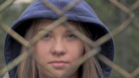Ritratto della ragazza caucasica bionda lunatica e triste dietro il recinto del ferro Giovane donna dietro la prigione di griglia archivi video