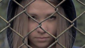 Ritratto della ragazza caucasica bionda lunatica e triste dietro il recinto del ferro Giovane donna dietro la prigione di griglia video d archivio