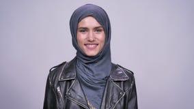 Ritratto della ragazza caucasica pura ed allegra nel hijab che ride francamente e che sorride sul fondo grigio stock footage