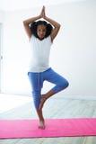 Ritratto della ragazza che fa yoga di posa dell'albero nella sala Immagine Stock