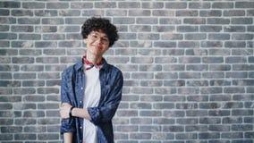 Ritratto della ragazza che gira che esamina macchina fotografica con il sorriso felice sul fondo del mattone stock footage