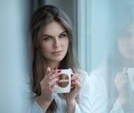 Ritratto della ragazza che gode della tazza di caffè Fotografia Stock