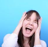Ritratto della ragazza che grida contro il fondo blu Fotografia Stock Libera da Diritti