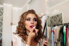 Ritratto della ragazza che mette rossetto sulle sue labbra e che guarda in specchio immagini stock