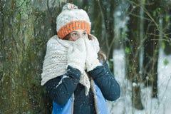Ritratto della ragazza che nasconde il suo fronte con la sciarpa ingombrante tricottata lanosa durante le precipitazioni nevose d Fotografia Stock